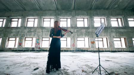 hegedűművész : One woman plays violin by notes in ruined building.