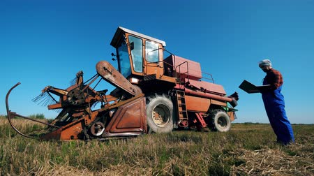 комбинированный : Agriculturist is looking at the combined harvester