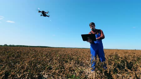 biologa : Male agronomist is navigating a drone from the computer