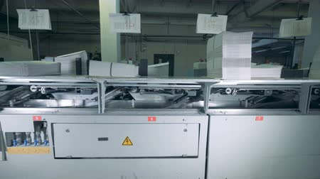 nakladatelství : Printed pieces of paper are moving through a printing press