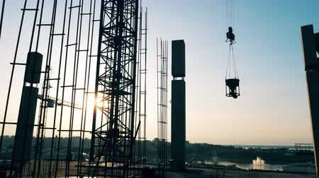 monolith : Crane moves construction parts while building a house. Stock Footage