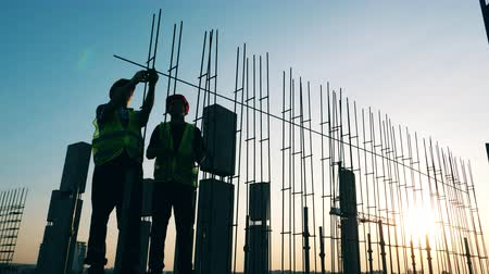 monolith : Engineers work with metal constructions while building a house. Stock Footage