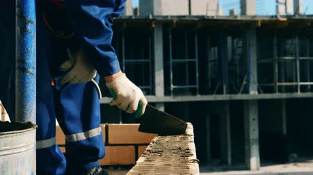 alvenaria : Worker uses cement to lay bricks while building a house. Stock Footage