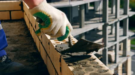 palette knife : A contractor works with brick wall, building a house. Stock Footage