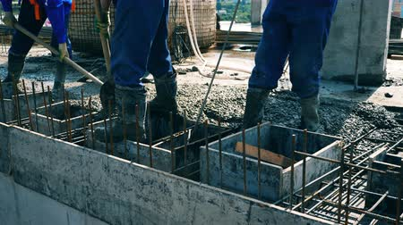 workman : Builders level cement on a floor while working at a construction site. Stock Footage