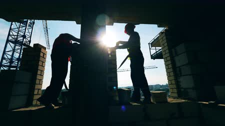 kielnia : People work at a building site, laying bricks.