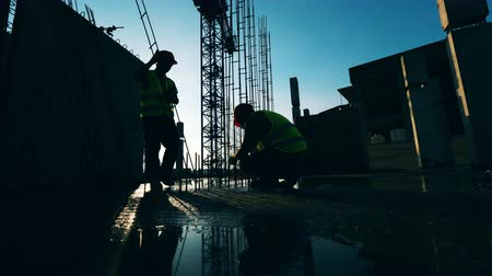 monolith : Two builders work with metal construction at a site. Stock Footage