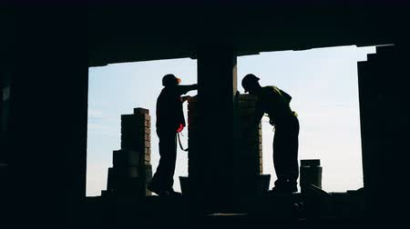 stuccatore : Workers lay bricks on a sky background.