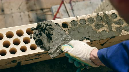 construct : A man uses a trowel while laying bricks.