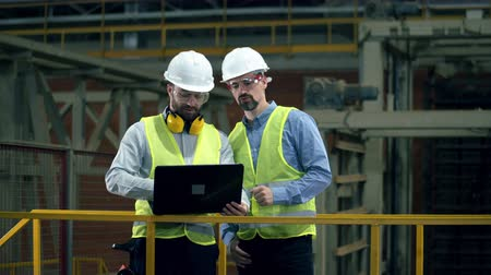 brick factory : Engineers work with a laptop at a brick plant.