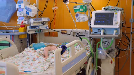 neonatology : Child lying in a bed in a hospital ward, undergoing a therapy.