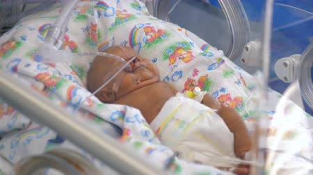 neonatology : A newborn baby with tubes lying in a medical incubator.