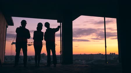 toezicht : Sunset construction site with architects having a discussion in it Stockvideo
