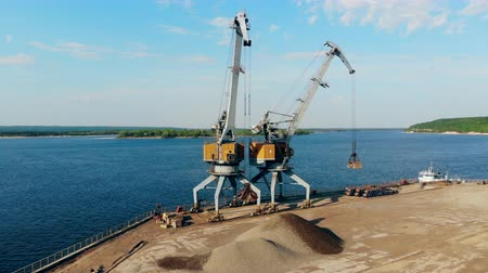 descarga : Two vehicles are transporting gravel at the cargo port
