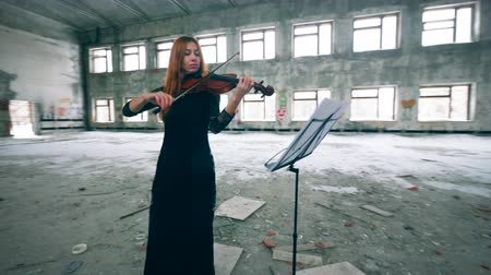 cellist : Redhead lady is playing the violin in a stranded building