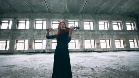 hegedűművész : Beautiful woman is playing the violin in an abandoned building
