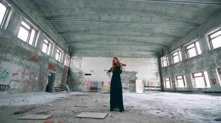 desolado : Unkempt hall with a female violinist playing the instrument Stock Footage