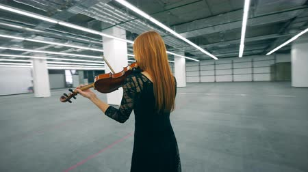 hegedűművész : Spacious empty hall with a woman playing the violin