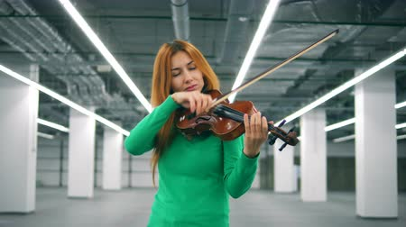 концерт : Lovely woman is playing the violin with pleasure