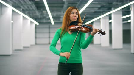 виолончель : Beautiful lady is playing the violin in an empty hall
