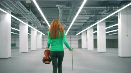 cellist : A woman with a violin is smiling and walking away Stock Footage