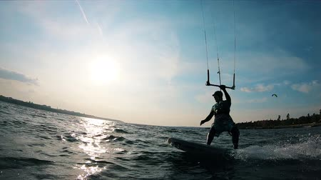 kiting : Male kiter is riding a board across the water