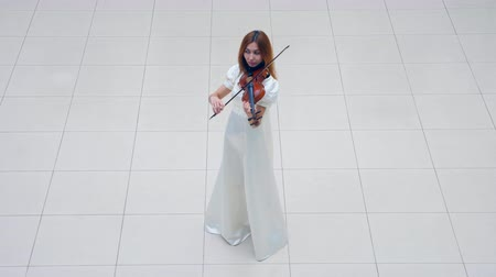 sofisticado : Woman in a white dress is skillfully playing the violin