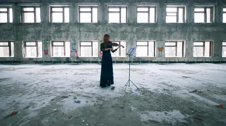 cellist : Abandoned building with a woman playing the violin