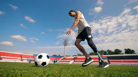 inwalida : Handicapped athlete is hitting a football