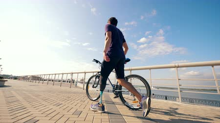 paralympic : A man with a bionic leg is wheeling a bike along the quay Stock Footage