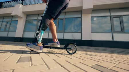 paralympic : Athlete with a prosthetic leg is riding a scooter