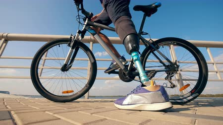 paralympics : Athlete with a prosthetic leg is getting on a bike Stock Footage