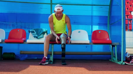 desvantagem : Removal of a prosthetic leg done by a male paralympian