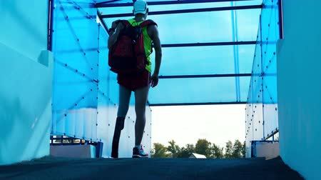 paralympic : A man with a prosthetic leg is fixing a backpack while walking Stock Footage