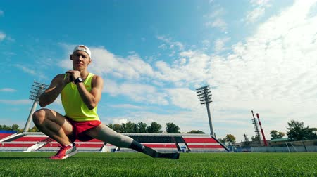 paralympic : Stadium and an athlete with a prosthetic leg working out on it
