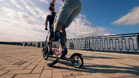 paralympic : People with prosthetic legs are riding scooters along the road Stock Footage
