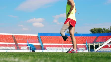 paralympic : Athlete with an artificial leg is stretching at the stadium Stock Footage