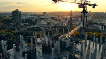 inacabado : High-rise building in progress with machinery at sunset. Modern Construction Site at sunset, aerial view.