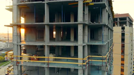 kader : Aerial view of construction site. The sun is shining through the floors of a building in progress Stockvideo