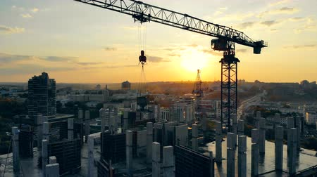 kader : Building crane and multistory house in progress at sunset Stockvideo
