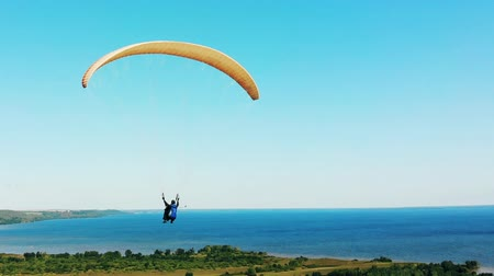 hang gliding : One athlete exercising with paraglider over fields.