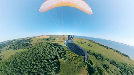 szybowiec : Person flies with yellow glider in blue sky.