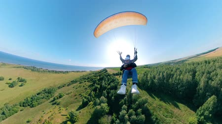 padák : Sports people flying with paraglider over fields.