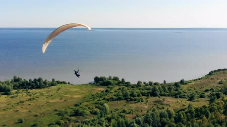 ugró : Sportsman flying with paraglider over a field.