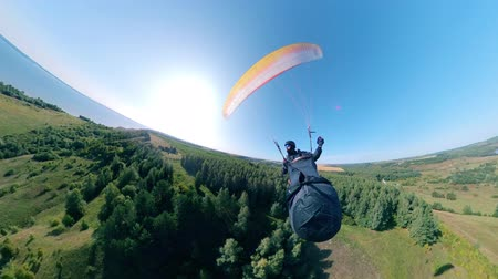 padák : Athlete training with paraglider, flying over fields.