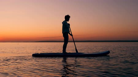 sucção : A boy is paddleboarding across the sunset lake Stock Footage