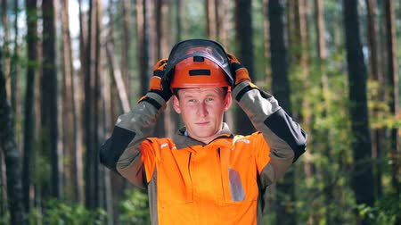 hardhat : Lumberman is putting on a hardhat
