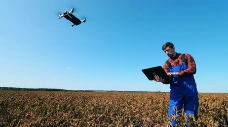 agronomist : Agricultural worker uses laptop to control drone while standing on a field.