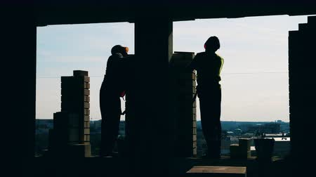 kőműves : Two builders lay bricks while working on a construction site. Stock mozgókép