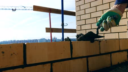 unfinished : One person lays bricks while building a house. Bricklayer doing brickwork at a construction site.